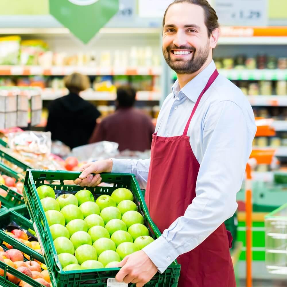 Chef de rayon fruits et légumes qui met des pommes locales en rayon